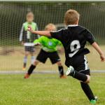 Un giovane calciatore sta per tirare in porta